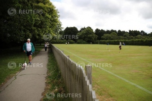 A man walks a dog on a path as people play croquet at Chester Croquet Club in Westminster Park, following the outbreak of the coronavirus disease (COVID-19), Chester, Britain, June 12, 2020. REUTERS/Molly Darlington